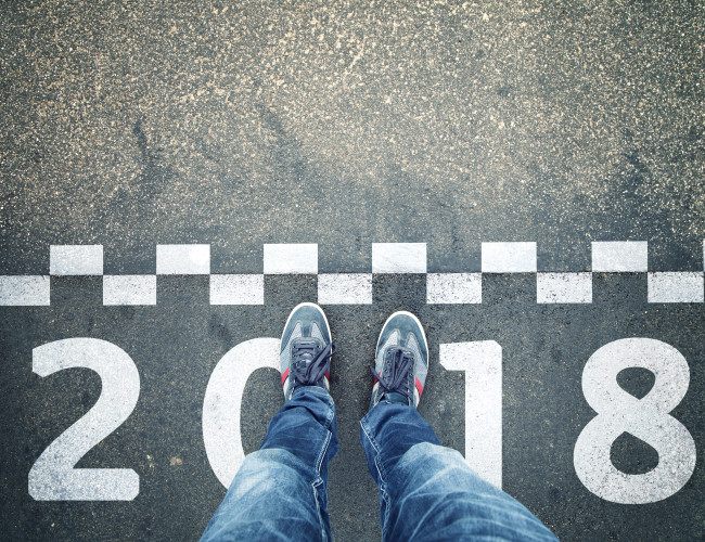 Person standing in front of a start New Year 2018 sign painted on asphalt city street. Point of view perspective used.